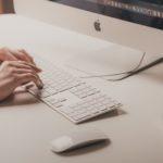 Person tippt auf Tastatur vor Computer